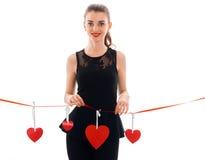 La fille gaie de brune dans la robe noire avec gentil composent pour célébrer le jour de valentines avec le coeur rouge dans le s Photo stock