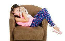 La fille gaie gaie d'enfant joue avec un petit chaton sur un fond clair Images stock
