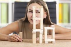 La fille gaie joue avec les briques en bois Image stock