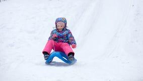 La fille gaie montant un traîneau en descendant sur une neige a couvert la traînée de traîneau dans un paysage ensoleillé blanc d Image stock