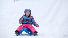 La fille gaie montant un traîneau en descendant sur une neige a couvert la traînée de traîneau dans un paysage ensoleillé blanc d Photo stock