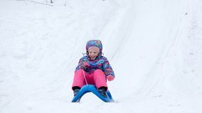 La fille gaie montant un traîneau en descendant sur une neige a couvert la traînée de traîneau dans un paysage ensoleillé blanc d Photographie stock libre de droits