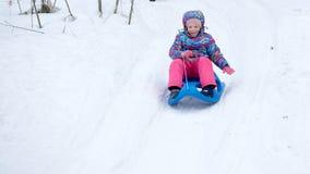 La fille gaie montant un traîneau en descendant sur une neige a couvert la traînée de traîneau dans un paysage ensoleillé blanc d Photographie stock