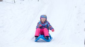 La fille gaie montant un traîneau en descendant sur une neige a couvert la traînée de traîneau dans un paysage ensoleillé blanc d Image libre de droits