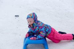 La fille gaie montant un traîneau en descendant sur une neige a couvert la traînée de traîneau dans un paysage ensoleillé blanc d Photos libres de droits