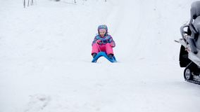La fille gaie montant un traîneau en descendant sur une neige a couvert la traînée de traîneau dans un paysage ensoleillé blanc d Photo libre de droits