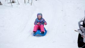 La fille gaie montant un traîneau en descendant sur une neige a couvert la traînée de traîneau dans un paysage ensoleillé blanc d Images stock