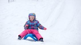La fille gaie montant un traîneau en descendant sur une neige a couvert la traînée de traîneau dans un paysage ensoleillé blanc d Images libres de droits