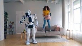La fille gaie saute sur un divan tandis qu'un droid danse Robot, cyborg et concept humain banque de vidéos