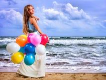 La fille garde les ballons colorés marchent sur la plage de mer Image libre de droits