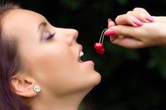 La fille goûtant une cerise Photos stock