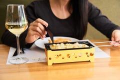 La fille goûte le raclette de fromage avec un verre de vin blanc dans un café Image libre de droits