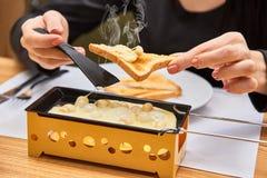 La fille goûte le raclette de fromage dans un café Délicieux et avec la vapeur chaude Photo stock