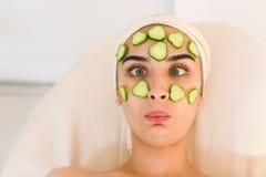 La fille grimace avec un masque de concombre sur son visage Photographie stock libre de droits