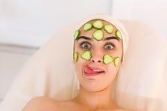 La fille grimace avec un masque de concombre sur son visage Photos stock