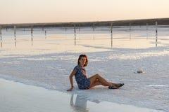 La fille heureuse appréciant le coucher du soleil, touche l'eau d'un lac de sel se reposant sur des cristaux image libre de droits