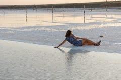 La fille heureuse appréciant le coucher du soleil, touche l'eau d'un lac de sel se reposant sur des cristaux photo libre de droits