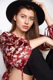 La fille heureuse attirante est possing et smilling dans la robe rouge de fleur et le chapeau noir sur le blanc Photographie stock