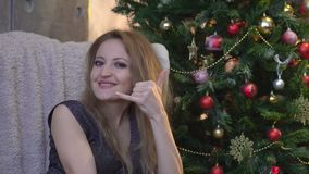 La fille heureuse attirante faisant des gestes avec des doigts m'appellent sur le fond d'arbre de Noël banque de vidéos