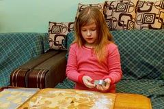 La fille heureuse avec la trisomie 21 fait des biscuits cuire au four Photos libres de droits