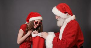 La fille heureuse choisit le cadeau dans le sac de Santa banque de vidéos