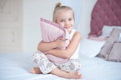 La fille heureuse d'enfant étreint l'oreiller se reposant sur le lit images stock