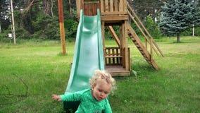 La fille heureuse d'enfant en bas âge glissent vers le bas sur le terrain de jeu d'enfant en parc banque de vidéos