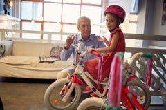 La fille heureuse d'enfant s'assied sur la bicyclette dans le magasin de v?lo avec son grand-p?re images libres de droits