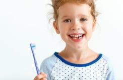 La fille heureuse d'enfant sourit avec la brosse à dents photo stock