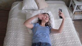 La fille heureuse dans des écouteurs avec le téléphone portable apprécient la musique tout en se reposant sur le lit à la ma clips vidéos