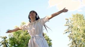 La fille heureuse dans des écouteurs sourit, tenir un smartphone dans des ses mains est dansant et tournant en parc d'été Beau banque de vidéos