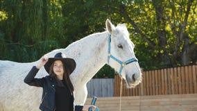 La fille heureuse dans le chapeau pose avec le sourire au cheval aimable blanc sur l'arène banque de vidéos