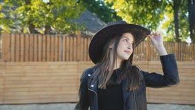 La fille heureuse dans le chapeau pose avec le sourire au cheval aimable blanc sur l'arène clips vidéos