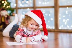 La fille heureuse dans le chapeau rouge de Noël écrit la lettre à Santa Claus Photo stock
