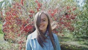 La fille heureuse dans un imperméable bleu marche par le parc de ressort après un arbre avec les fleurs rouges clips vidéos