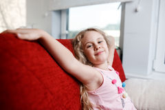 La fille heureuse de 6 ans s'assied sur la chaise rouge dans sa chambre Photographie stock