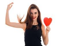 La fille heureuse de brune dans la robe noire avec gentil composent pour célébrer le jour de valentines avec le coeur rouge dans  Photographie stock libre de droits