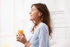 La fille heureuse de brune habillée dans le pyjama bleu-clair tient un verre de jus frais dans ses mains et sourires dans le conf photos libres de droits