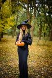 La fille heureuse de sorcière de Halloween conserve le potiron Image libre de droits
