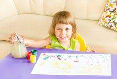 La fille heureuse dessine des peintures Photographie stock