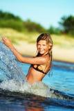 La fille heureuse effectuant l'eau éclabousse Image libre de droits
