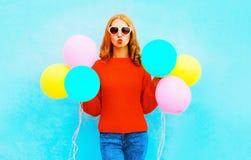 La fille heureuse fraîche fait un baiser d'air avec les ballons colorés sur le bleu Images libres de droits