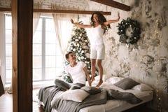 La fille heureuse habill?e dans les T-shirts blancs et les shorts saute sur le lit ? c?t? du type s'asseyant l? dans un confortab photo libre de droits