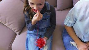 La fille heureuse mange la sucrerie rouge banque de vidéos