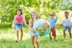 La fille heureuse porte le globe du monde Images libres de droits