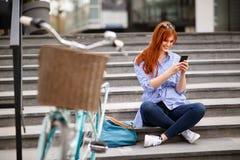 La fille heureuse regarde dans le téléphone portable images stock