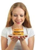 La fille heureuse regarde les aliments de préparation rapide, hamburger Photographie stock libre de droits