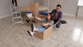 La fille heureuse s'asseyant dans une boîte en carton, les couples est entrée dans une nouvelle maison banque de vidéos
