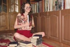 La fille heureuse s'assied en position de lotus et tient un livre concernant l'art avec deux mains dans la bibliothèque Images stock