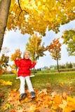 La fille heureuse s'assied sur des oscillations souriant pendant l'automne Image libre de droits